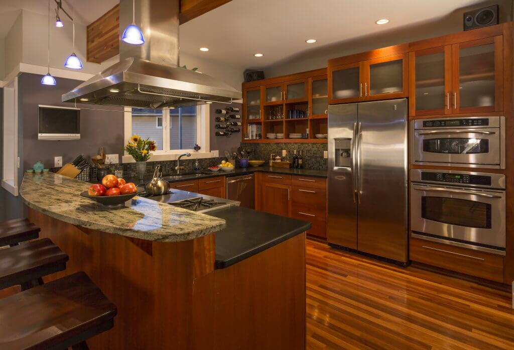 Contemporary upscale home kitchen interior with wood cabinets and floors, granite countertop, accent lighting, television & stainless steel appliances including double oven, refrigerator and vent hood